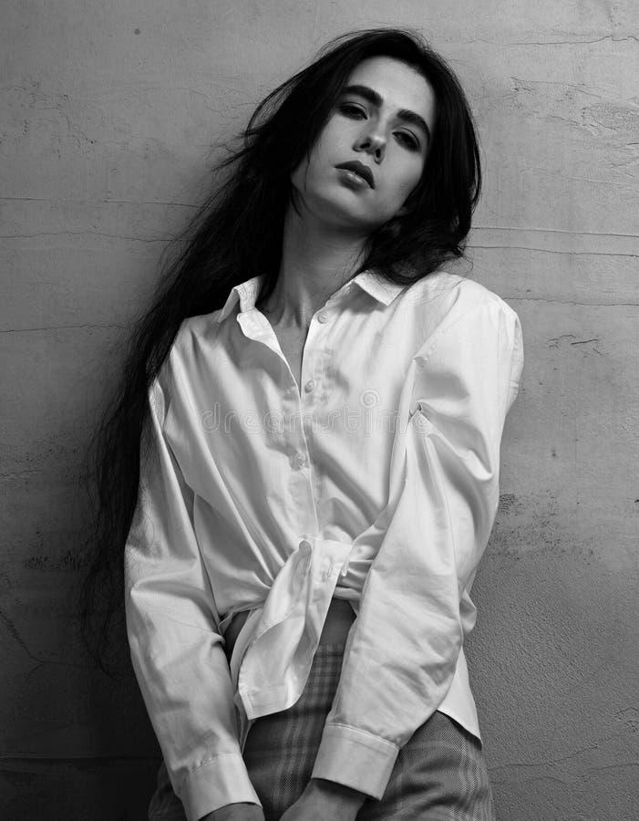 Mujer de pensamiento joven de la depresión triste que presenta en falda roja y la camisa blanca en fondo gris del estudio de la p imagen de archivo