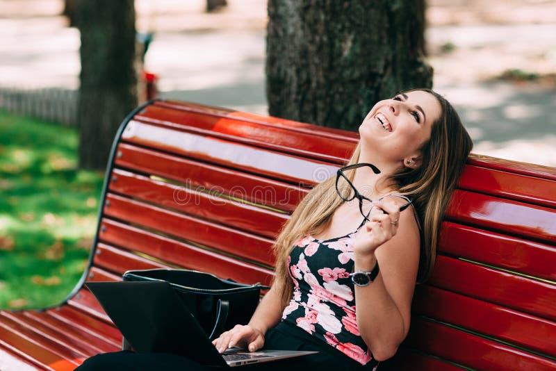 Mujer de risa con los vidrios y el funcionamiento del ordenador portátil imagenes de archivo