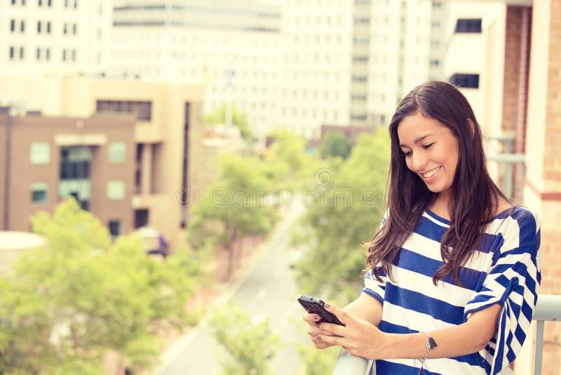 Mujer de risa emocionada feliz que manda un SMS en el teléfono móvil foto de archivo libre de regalías