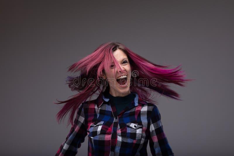 Mujer de risa feliz que chasquea su pelo en el aire imagen de archivo libre de regalías