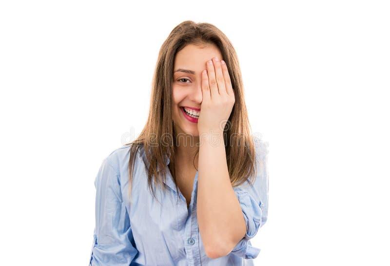 Mujer de risa joven que cubre un ojo fotos de archivo