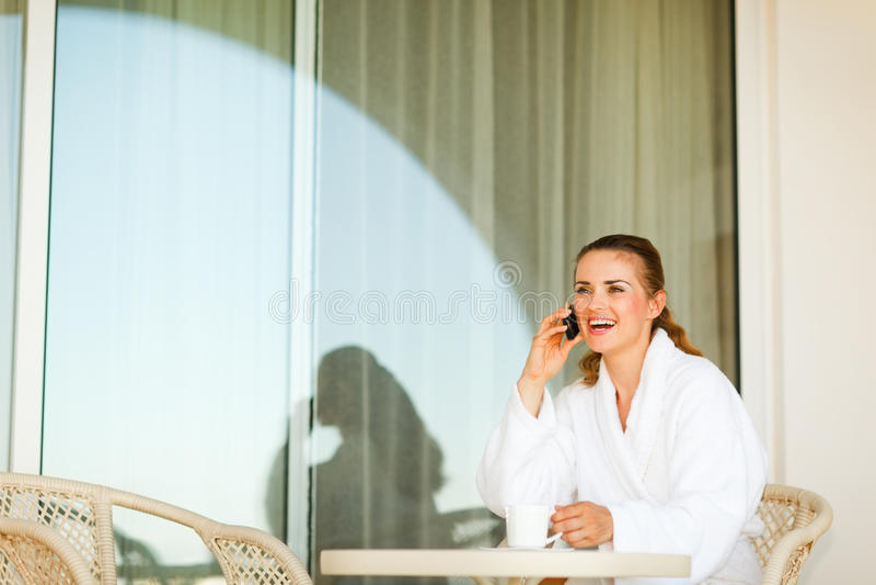 Mujer de risa que come café en terraza imagenes de archivo
