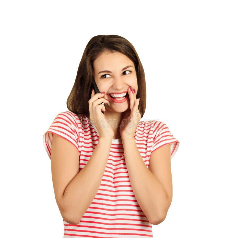Mujer de risa que habla en el teléfono muchacha emocional aislada en el fondo blanco imagenes de archivo