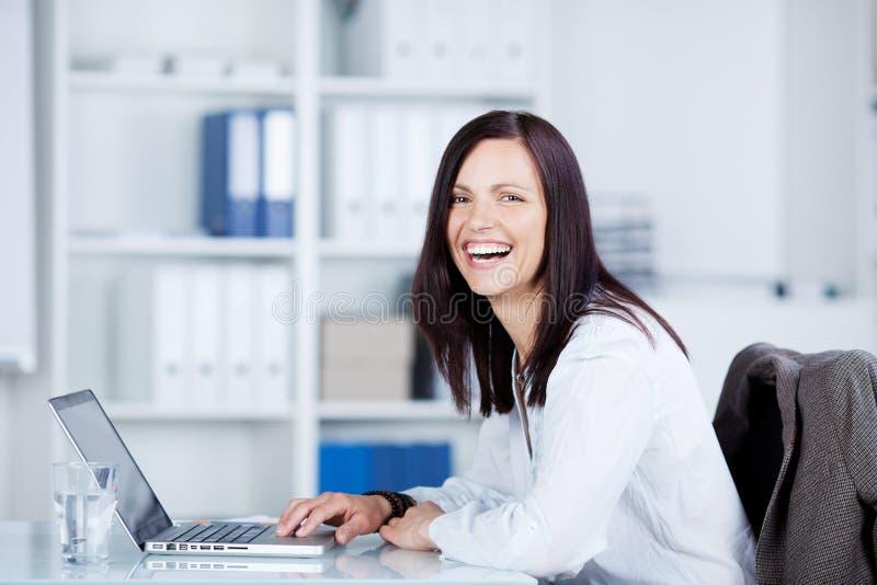 Mujer de risa que usa un ordenador portátil imagen de archivo