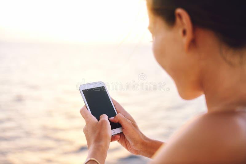 Mujer de Smartphone que manda un SMS en los medios sociales app fotografía de archivo