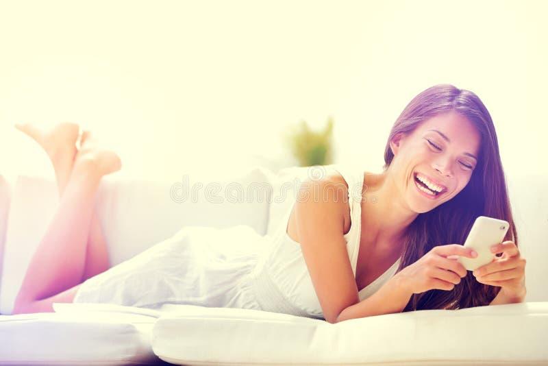 Mujer de Smartphone que usa el app en la sonrisa del teléfono feliz imagen de archivo libre de regalías