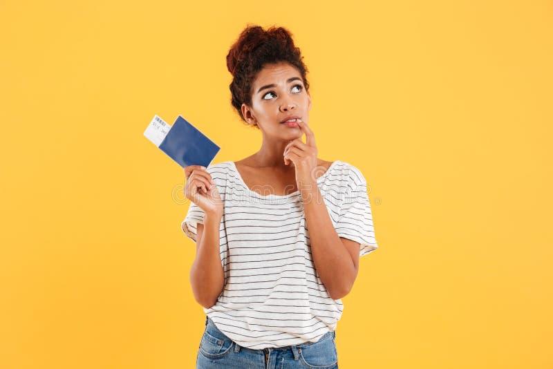 Mujer de Thoghtful que sostiene el pasaporte internacional aislado sobre amarillo foto de archivo