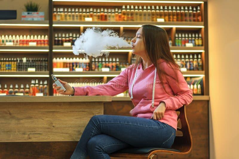 Mujer de Vape Muchacha linda joven en la sudadera con capucha rosada que fuma un cigarrillo electrónico foto de archivo