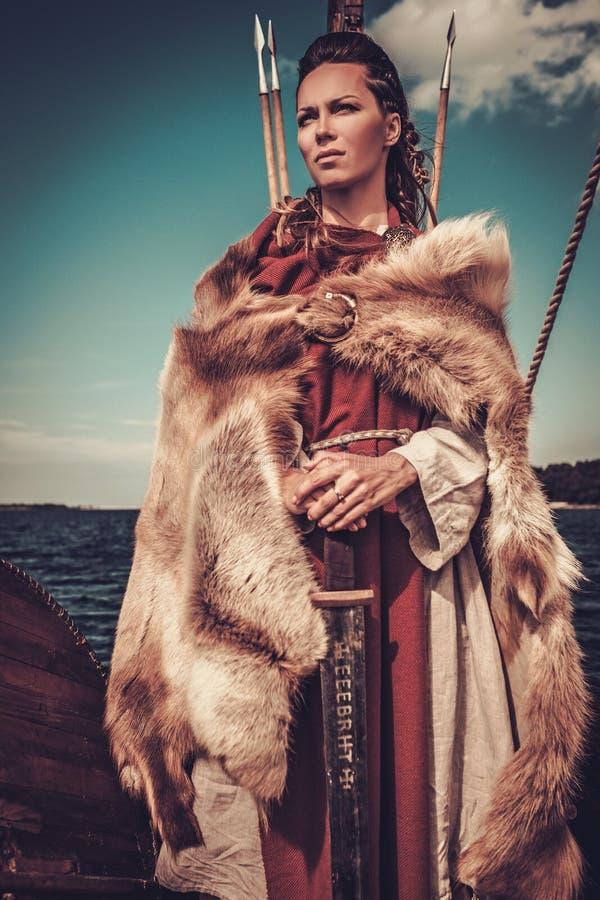 Mujer de Viking con la espada y el escudo que se colocan en Drakkar imagen de archivo