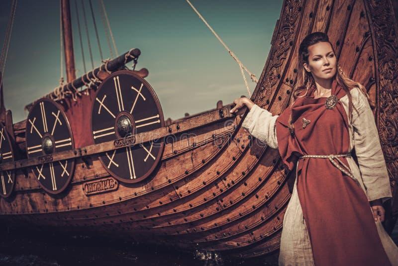 Mujer de Viking que se coloca cerca de Drakkar en la costa imágenes de archivo libres de regalías