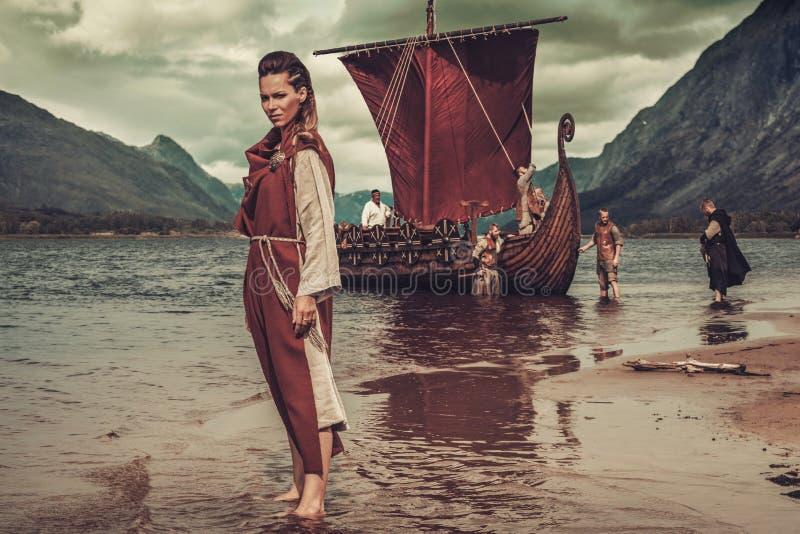 Mujer de Viking que se coloca cerca de Drakkar en la costa imagen de archivo