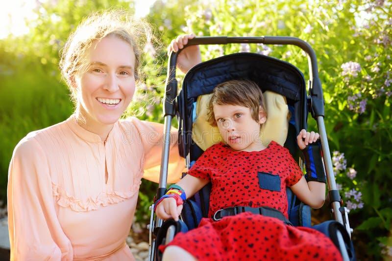 Mujer de Yong con la muchacha discapacitada en una silla de ruedas que camina en el parque del verano fotografía de archivo