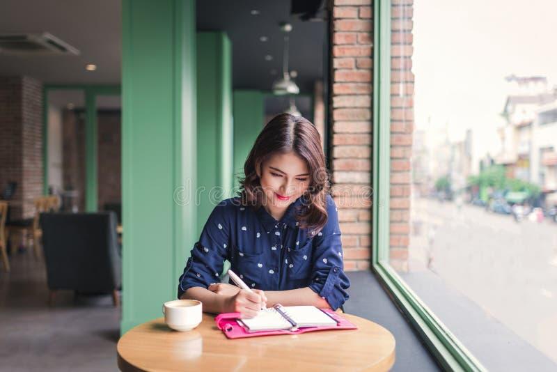 Mujer de Yong del asiático en el café cerca de la ventana, del pensamiento y del writi fotografía de archivo