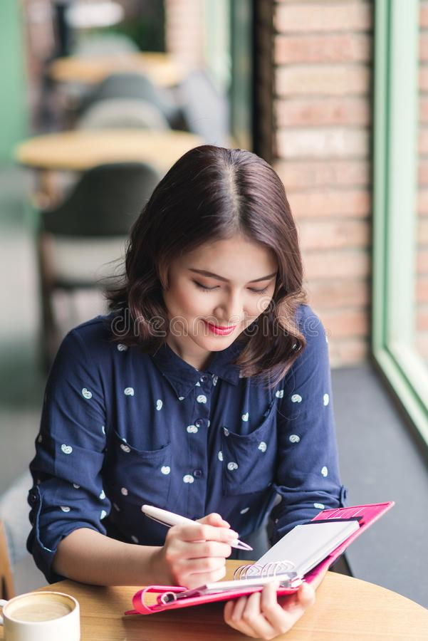 Mujer de Yong del asiático en el café cerca de la ventana, del pensamiento y del writi imagen de archivo