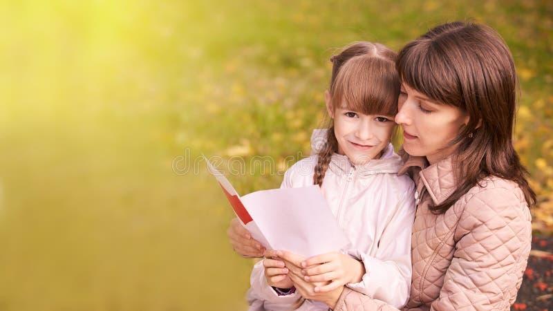 Mujer de Youn con la hija outdoors Fondo del oto?o D?a de la madre foto de archivo