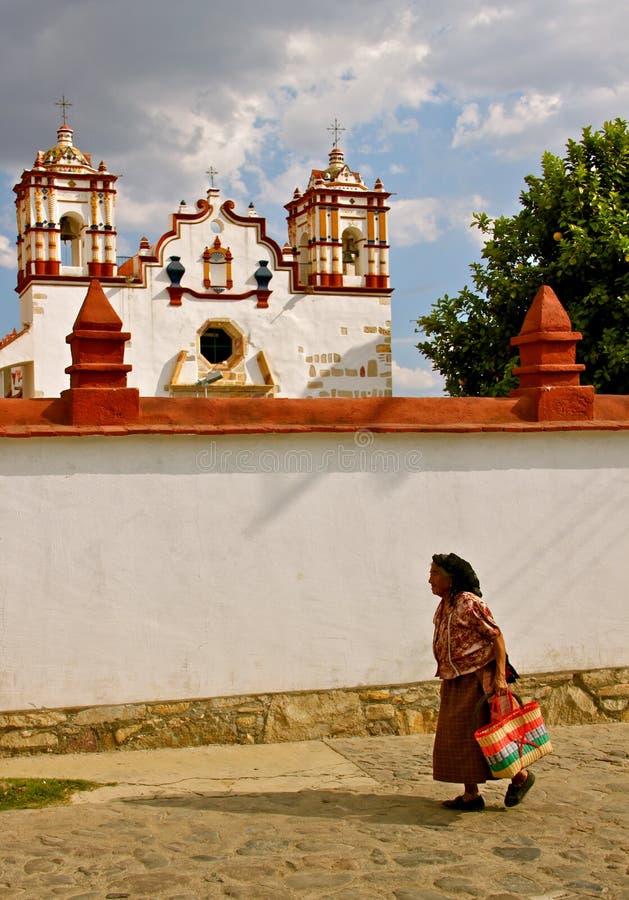 Mujer de Zapotec que pasa la iglesia de Teotitlán, México imagen de archivo