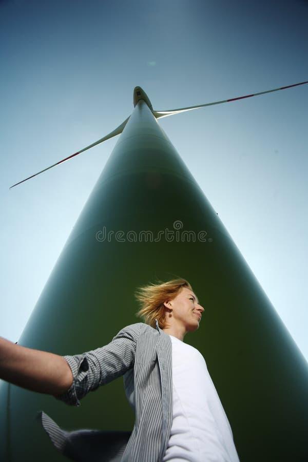 Mujer debajo de la turbina de viento foto de archivo