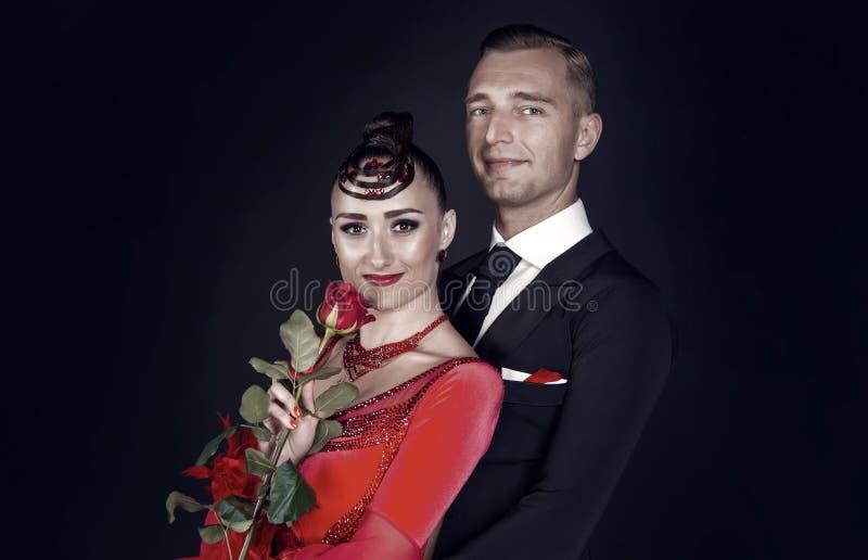 Mujer del abrazo del hombre con la flor de la rosa del rojo foto de archivo libre de regalías