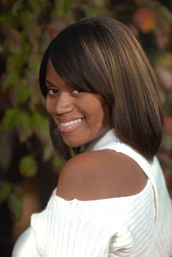 Mujer del African-American que mira una sonrisa fotografía de archivo