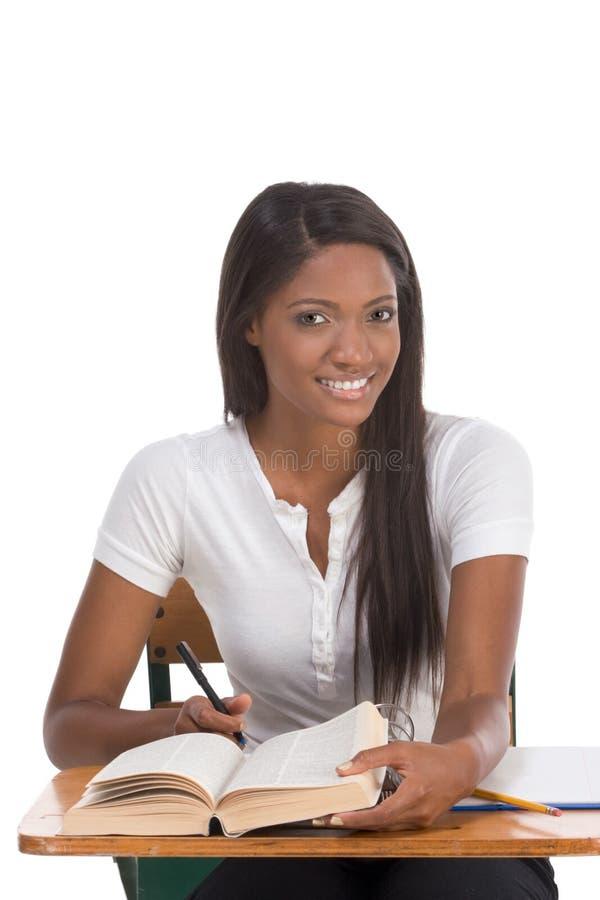 Mujer del afroamericano del estudiante universitario por el escritorio fotografía de archivo