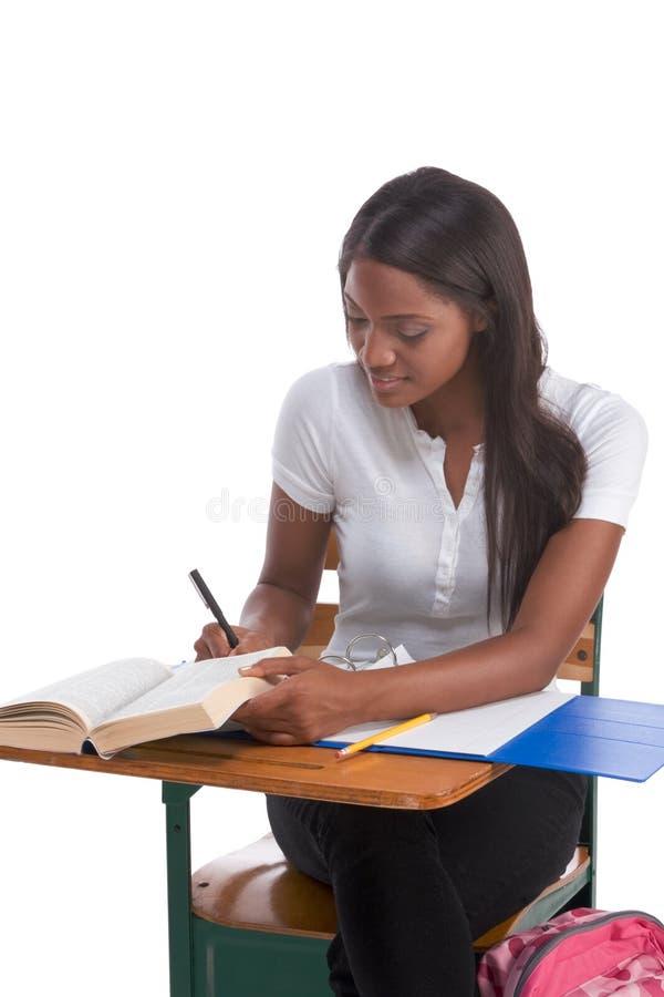 Mujer del afroamericano del estudiante universitario por el escritorio fotos de archivo libres de regalías