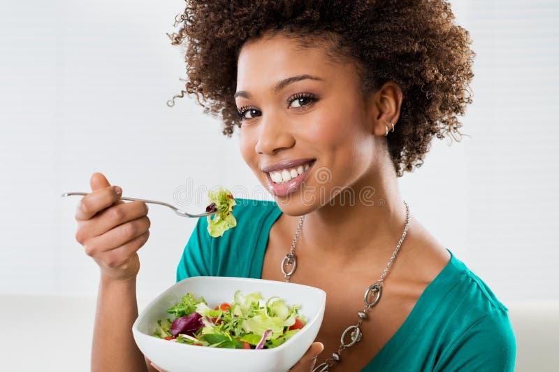 Mujer del afroamericano que come la ensalada imagenes de archivo