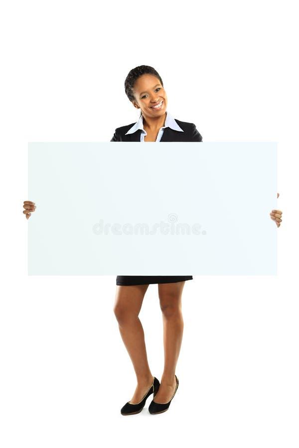 Mujer del afroamericano que lleva a cabo un espacio en blanco imagen de archivo