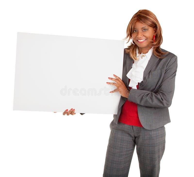 Mujer del afroamericano que lleva a cabo una muestra blanca en blanco fotos de archivo