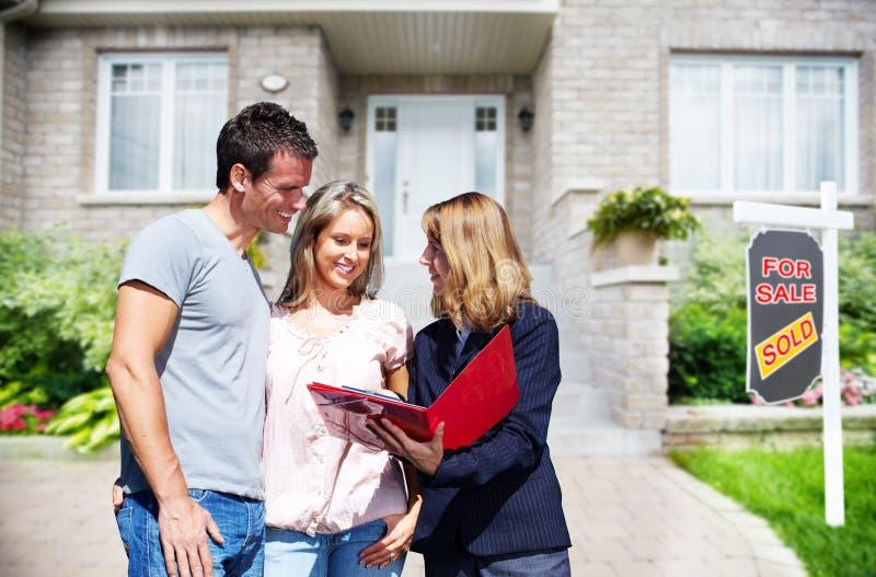 Mujer del agente inmobiliario con los clientes cerca de la nueva casa fotos de archivo libres de regalías
