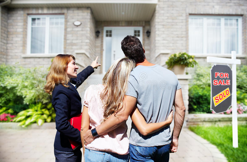 Mujer del agente inmobiliario con los clientes cerca de la nueva casa foto de archivo libre de regalías