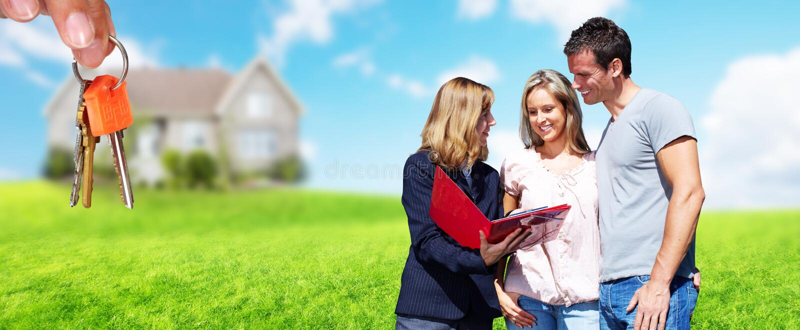 Mujer del agente inmobiliario con los clientes cerca de la nueva casa imagen de archivo libre de regalías
