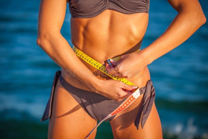 Mujer del ajustado en bikini con la cinta de la medida fotos de archivo libres de regalías