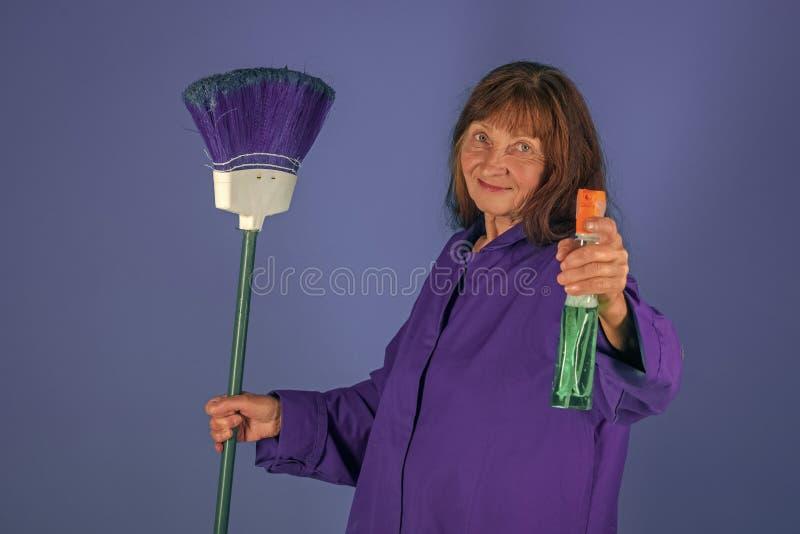 Mujer del ama de casa en uniforme con el espray limpio fotos de archivo