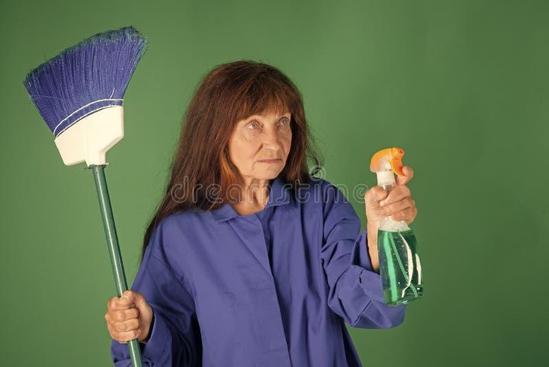 Mujer del ama de casa en uniforme con el espray limpio imagen de archivo