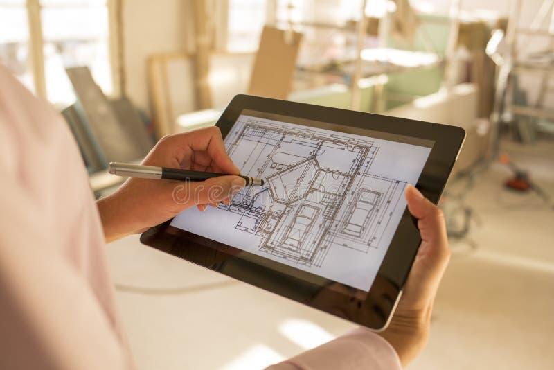 Mujer del arquitecto que trabaja con la tableta electrónica fotos de archivo
