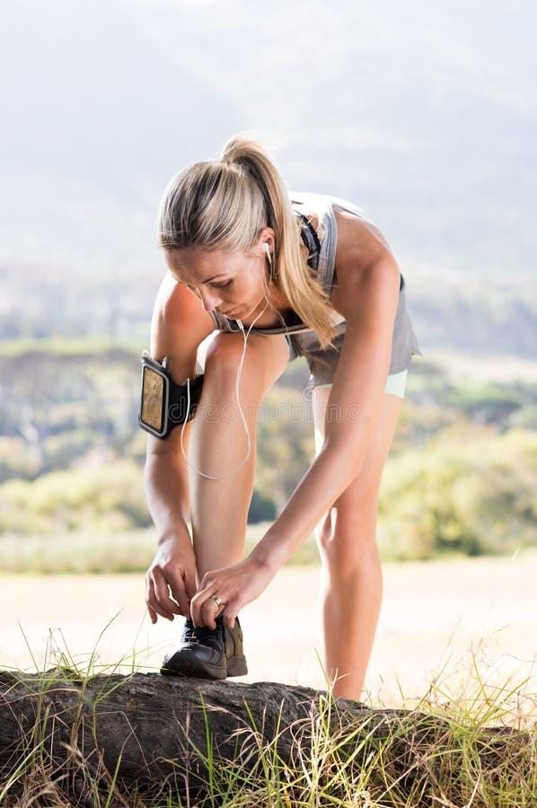 Mujer del atleta que ata el cordón fotos de archivo