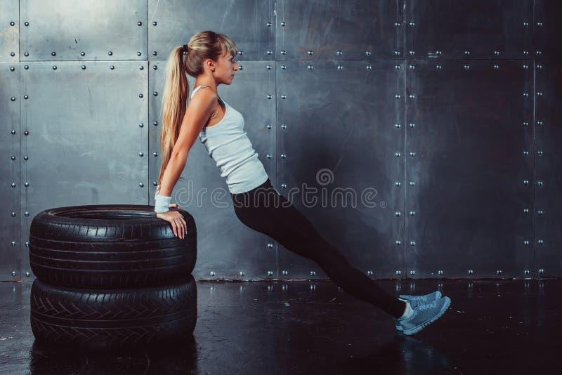 Mujer del atleta que hace pectorales en el entrenamiento del banco imagen de archivo