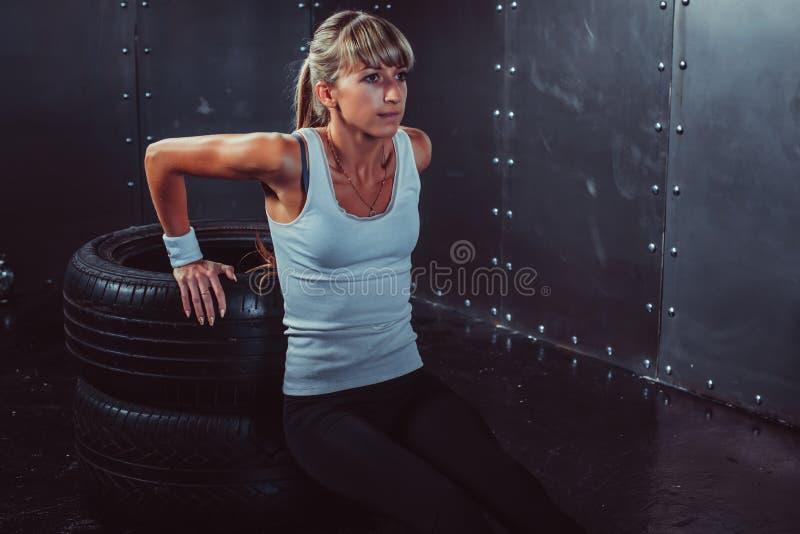 Mujer del atleta que hace pectorales en el entrenamiento del banco foto de archivo
