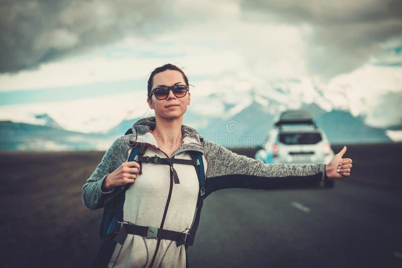 Mujer del autostopista del viaje que camina en un camino foto de archivo