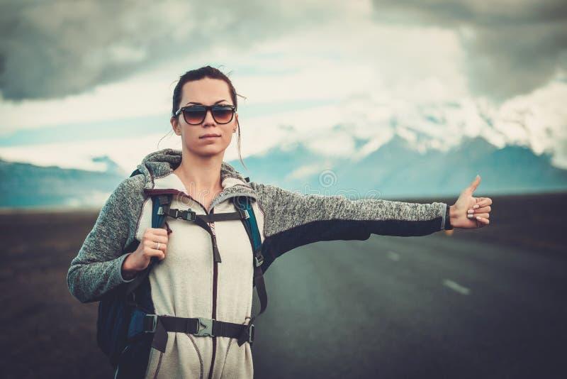 Mujer del autostopista del viaje que camina en un camino fotografía de archivo libre de regalías