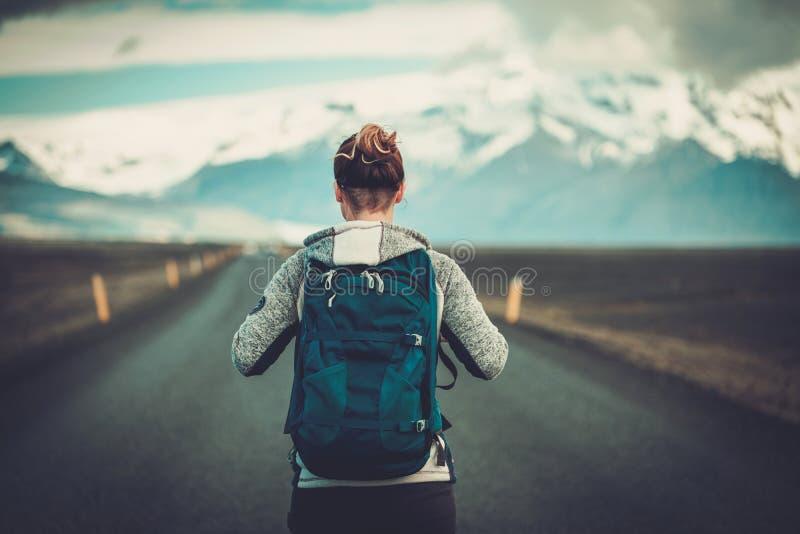 Mujer del autostopista del viaje que camina en un camino imágenes de archivo libres de regalías