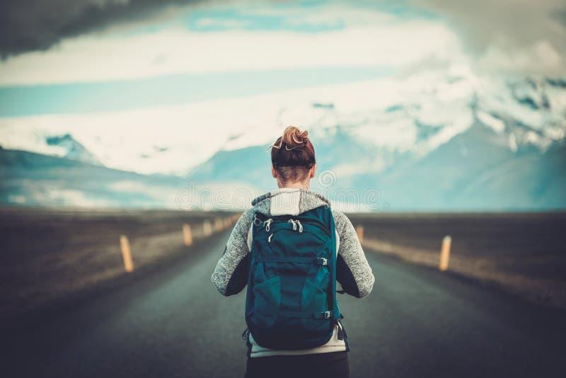 Mujer del autostopista del viaje que camina en un camino fotografía de archivo