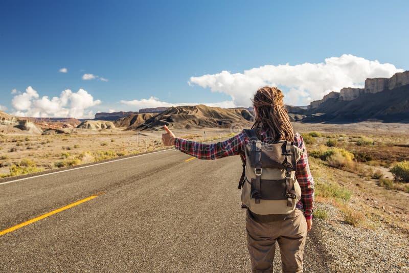 Mujer del autostopista que camina en un camino en los E.E.U.U. imagen de archivo