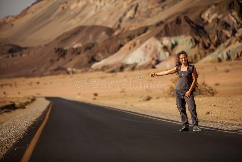Mujer del autostopista que camina en un camino en los E.E.U.U. foto de archivo