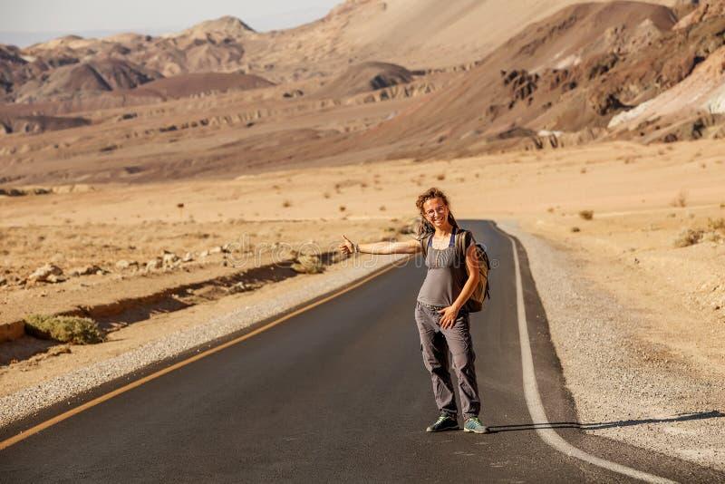 Mujer del autostopista que camina en un camino en los E.E.U.U. fotografía de archivo