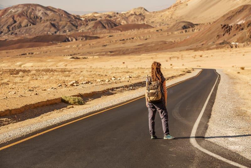 Mujer del autostopista que camina en un camino en los E.E.U.U. fotos de archivo