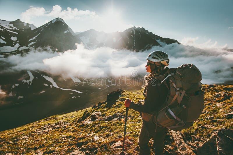 Mujer del Backpacker que goza de las nubes de las montañas fotografía de archivo