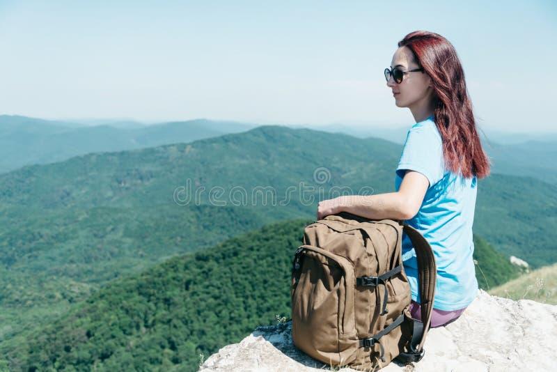 Mujer del Backpacker que se sienta arriba en montañas del verano imagen de archivo libre de regalías