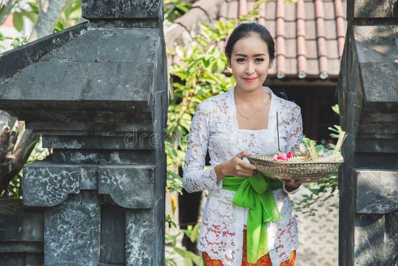 Mujer del Balinese que lleva la ropa tradicional que trae la sari del canang imagen de archivo