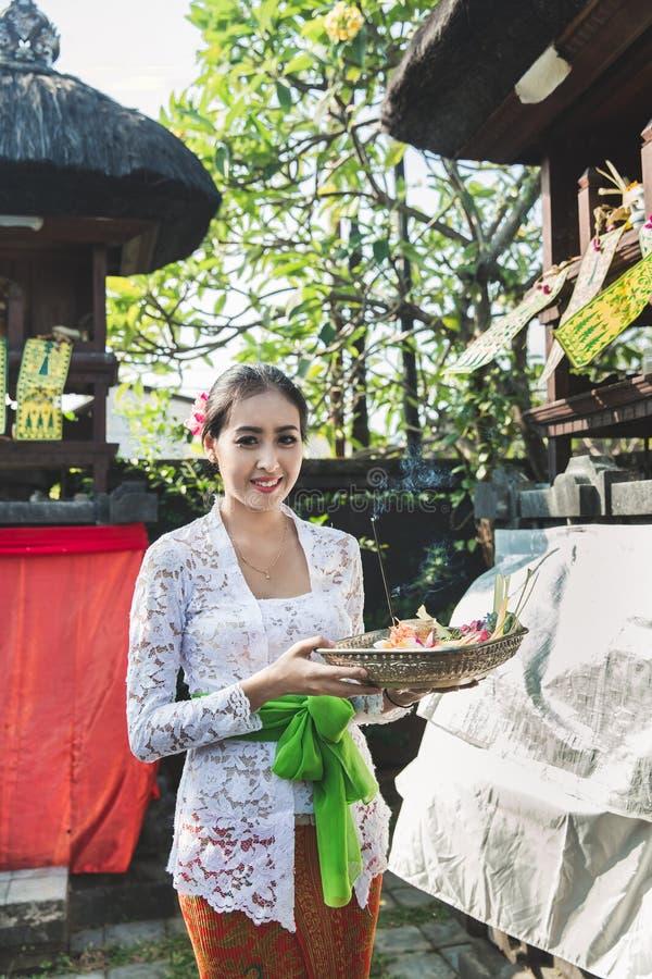 Mujer del Balinese que lleva la ropa tradicional que trae la sari del canang fotos de archivo libres de regalías